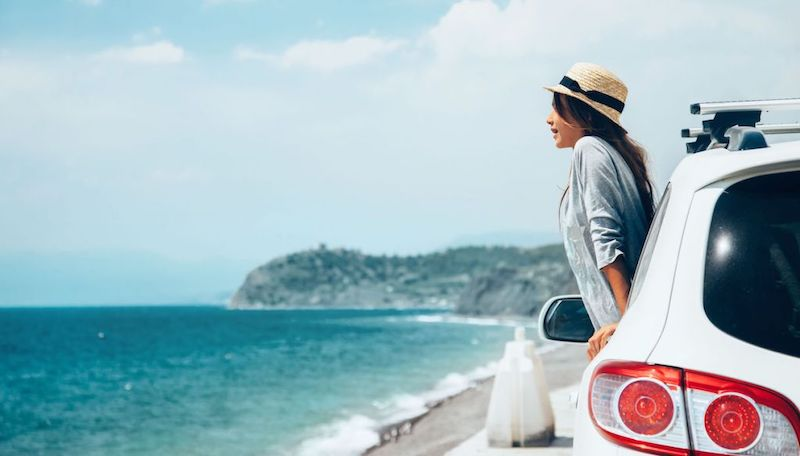 Mulher no carro na praia